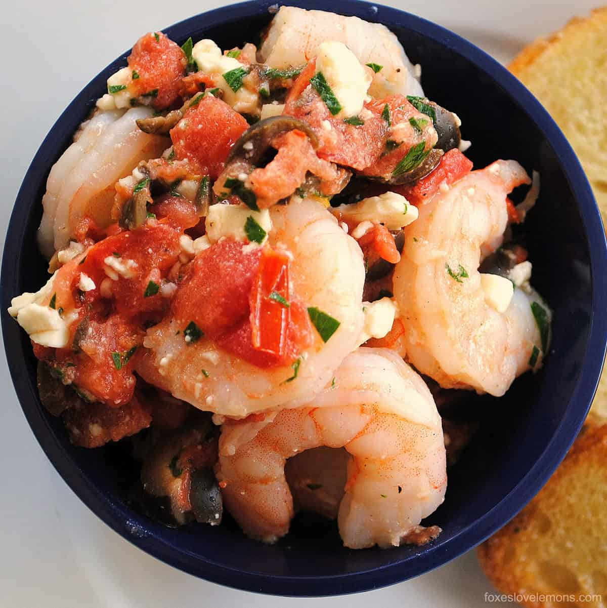 Greek Shrimp Bruschetta - Perfect for a party! Sauteed shrimp with olives, tomato, feta and capers. Serve with crunchy bruschetta.