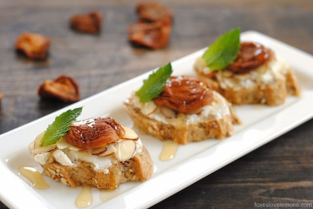 Apricot-Ricotta Crostini - multigrain baguette slices topped with ricotta, almonds, apricots and honey. A perfect bite for dessert or cocktail hour!
