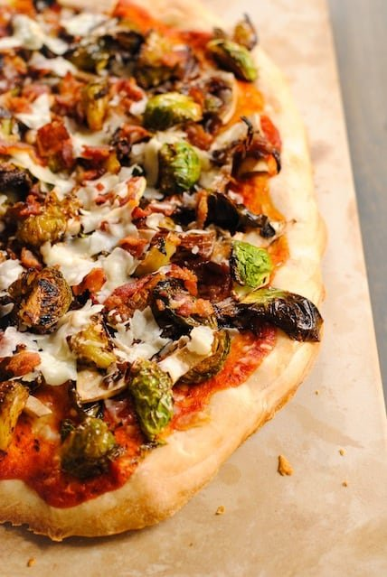 Bacon & Brussels Pizza - thin pizza crust topped with roasted brussels sprouts, crispy bacon, caramelized onion, mushrooms and shaved Parmesan cheese.