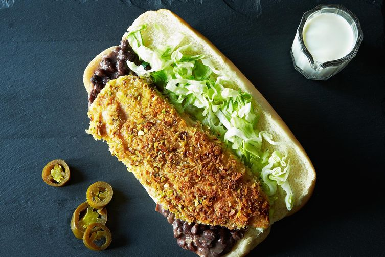 Pistachio-Crusted Chicken Tortas - Crispy baked chicken breasts topped with mashed black beans, jalapenos, lettuce, tomato and creamy avocado sauce.