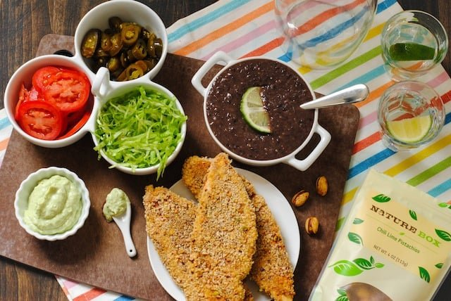 Pistachio-Crusted Chicken Tortas - Crispy baked chicken breasts topped with mashed black beans, jalapenos, lettuce, tomato and creamy avocado sauce.   foxeslovelemons.com