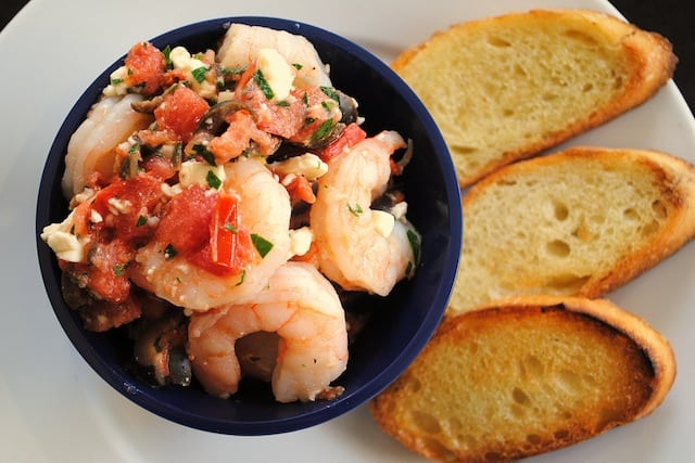 Greek Shrimp Bruschetta - Perfect for New Year's Eve! Sauteed shrimp with olives, tomato, feta and capers. Serve with crunchy bruschetta. | foxeslovelemons.com