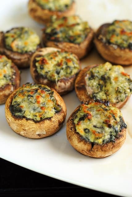 Spinach & Artichoke Stuffed Mushrooms - Perfect for New Year's Eve! An incredibly easy party food that uses a little help from the grocery store ;) | foxeslovelemons.com