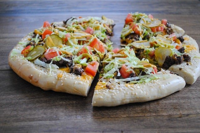 Cheeseburger Pizza - Ground beef, special sauce, lettuce, cheese, pickles, onions...on a sesame seed crust.