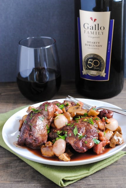 Classic Coq au Vin - Chicken, pancetta, mushrooms and pearl onions braised in red wine. Comfort food at it's finest. Perfect for a dinner party! | foxeslovelemons.com