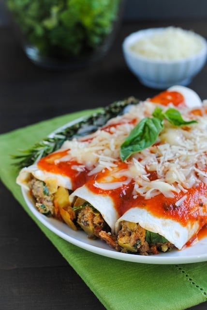 Italian Enchiladas - A tasty casserole (with hidden veggies!) the whole family will enjoy! Ground beef, Italian sausage, pepperoni, artichokes, spinach, mushrooms and ricotta cheese rolled up in flour tortillas, topped with marinara and mozzarella.
