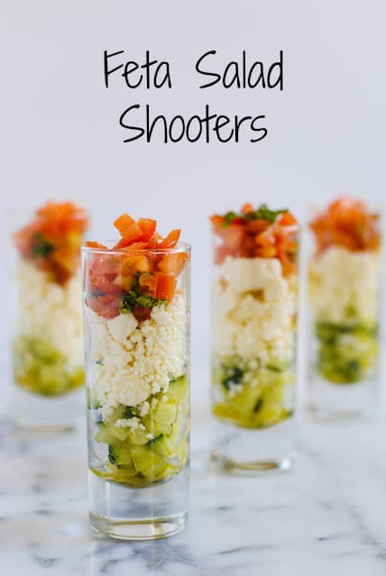 Feta Salad Shooters - layers of crunchy cucumber, tangy feta cheese, and fresh tomato and basil. A perfect, simple party bite for the summer!