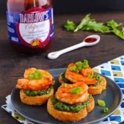 Chipotle Shrimp & Arugula Pesto Crostini - A fresh and elegant summer party bite. Crunchy bread, herby homemade arugula pesto, and chipotle glazed shrimp.   foxeslovelemons.com