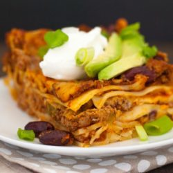 Gluten-Free Chili Lasagna - No matter your reason for skipping gluten, this casserole doesn't skip any flavor! Layers of pasta, hearty beef and bean chili, and Colby Jack cheese, topped with Greek yogurt and avocado! | foxeslovelemons.com
