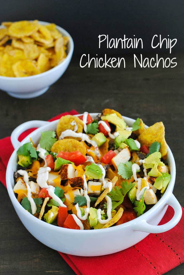 Plantain Chip Chicken Nachos - A pile of nachos created with crispy plantain chips, spice-rubbed chicken, black beans, cheddar cheese, avocado, tomato, cilantro and a spicy chipotle sour cream drizzle! | foxeslovelemons.com