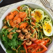 Zucchini Noodle Bowl with Spicy Cashew Sauce - Spiralized zucchini topped with carrots, red pepper, cilantro, a soft-boiled egg and an Asian-inspired spicy cashew sauce. | foxeslovelemons.com