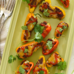 Black Bean Stuffed Mini Pepper Bites - A protein-packed snack, or fun party appetizer! Mini bell peppers stuffed with refried black beans and topped with cheese. | foxeslovelemons.com
