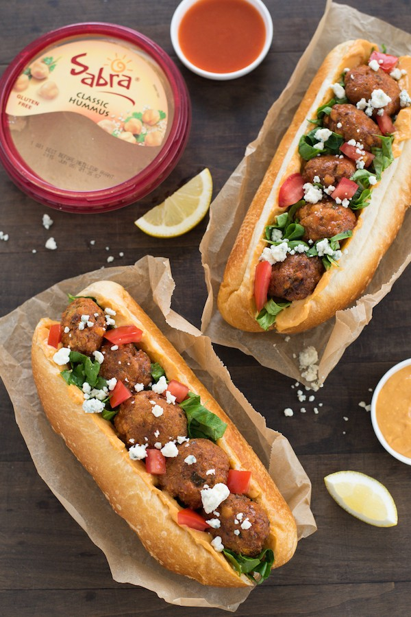 Buffalo Falafel Subs - Fried chickepea fritters are tossed in buffalo sauce then piled into subs with buffalo-flavored hummus, lettuce, tomato and blue cheese! | foxeslovelemons.com
