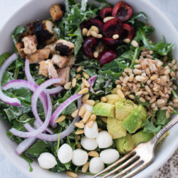 Chicken & Cherry Chopped Kale Salad with Pesto Ranch Dressing - A colorful and delicious mix of greens, chicken, cherries, farro, avocado, mozzarella cheese, red onions and pine nuts, tossed with homemade pesto ranch dressing! | foxeslovelemons.com