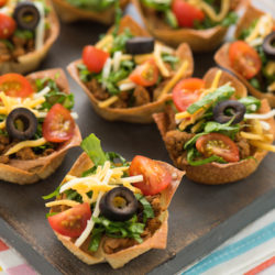 """Mini Turkey Taco Salads - An appetizer-sized version of the restaurant classic! Layers of beans, seasoned ground turkey, cheese, lettuce and tomato inside of wonton wrapper """"taco shell"""" bowls! 