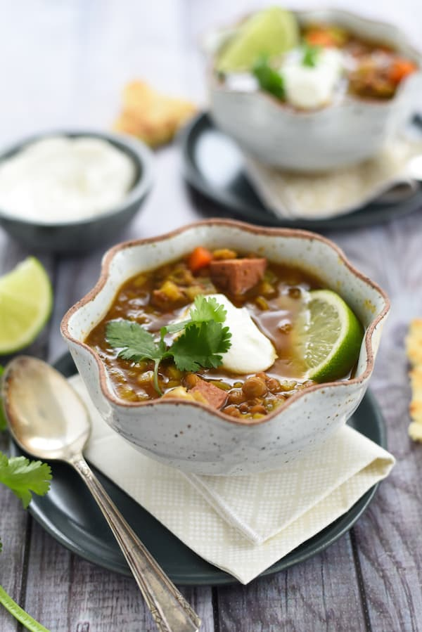 Slow cooker lentil soup with sausage in fluted bowl, topped with cilantro, yogurt and a lime wedge.