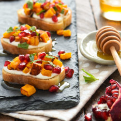Butternut Squash & Pomegranate Crostini with Whipped Feta and Honey - This autumn appetizer is the perfect balance of sweet and savory. Set these out at your next party and watch them disappear! | foxeslovelemons.com