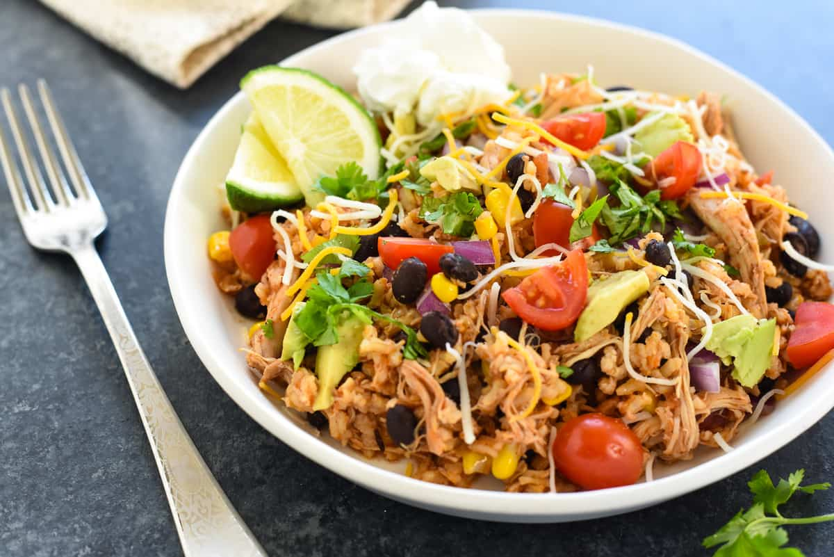Let your crockpot do the work for this Slow Cooker Chicken Burrito Bowl. A healthful weeknight meal with big flavor! The family will love these chicken, bean, corn and rice bowls topped with colorful garnishes. | foxeslovelemons.com