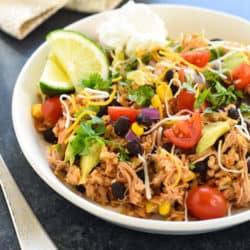 Slow Cooker Chicken Burrito Bowls - Let your crockpot do the work for this healthful meal with big flavors. Chicken, black beans, corn and brown rice are topped with an explosion of colorful garnishes! | foxeslovelemons.com