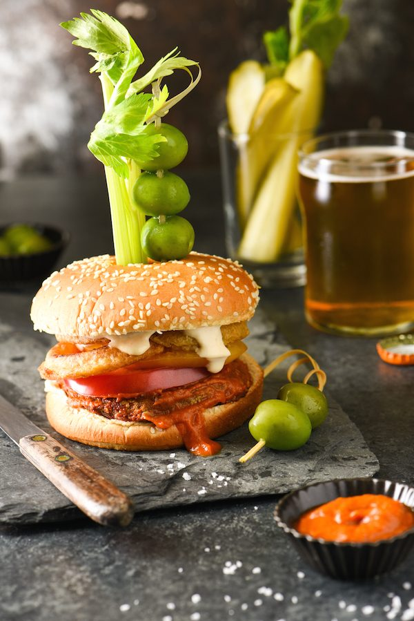Epic Bloody Mary Burgers - Bloody mary lovers, this burger is calling your name! The burger is slathered in bloody mary ketchup, then topped with onion rings, tomato slices and horseradish mayo. Skewer with celery, olives and pickles and dig in! | foxeslovelemons.com