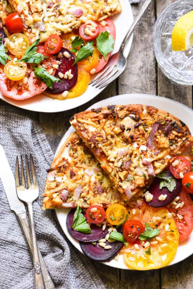Two plates filled with pizza slices and tomato and beet salad. Forks alongside.