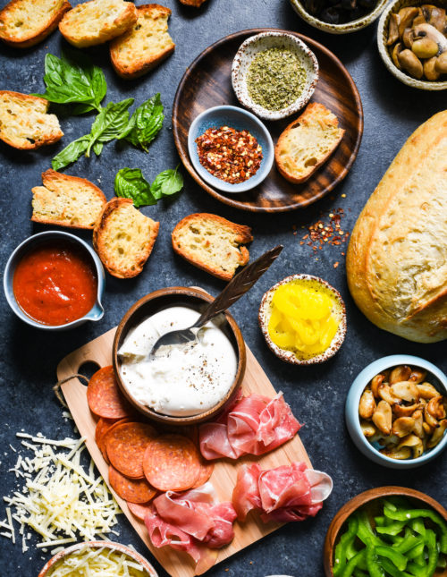 Pizza Crostini Bar - Put out some toasted bread and a big spread of pizza toppings, and let everybody make their own appetizer. So fun for parties! | foxeslovelemons.com