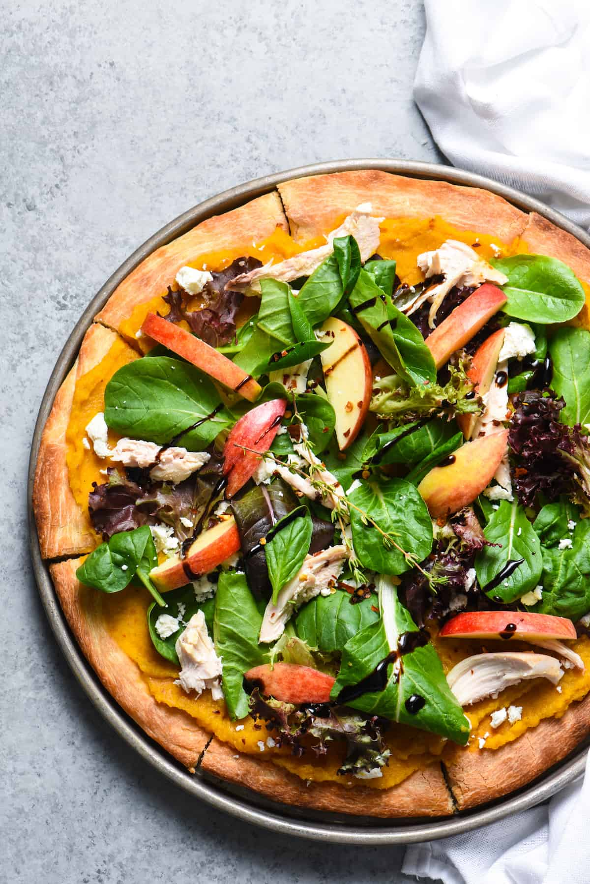 """This Fall Harvest Salad Pizza celebrates all the best fresh autumn produce. Use a roasted butternut squash and maple syrup puréeas the """"sauce"""" and top with a heaping helping of salad with chicken, cheese and apples! 