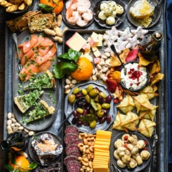 Feed a party crowd with this New Year's Eve Snack Board. Make all of your snacking dreams come true with cheese, crackers, quiche, spinach and artichoke wontons, smoked salmon, nuts, fruit, olives and a few sweet treats. | foxeslovelemons.com