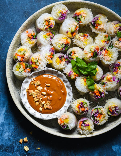 "Serve the rainbow with these Salmon Fresh Rolls with Spicy Peanut Sauce. Perfect as a bright party appetizer or healthful dinner, be a ""home chef"" and make this takeout-inspired recipe at home! 
