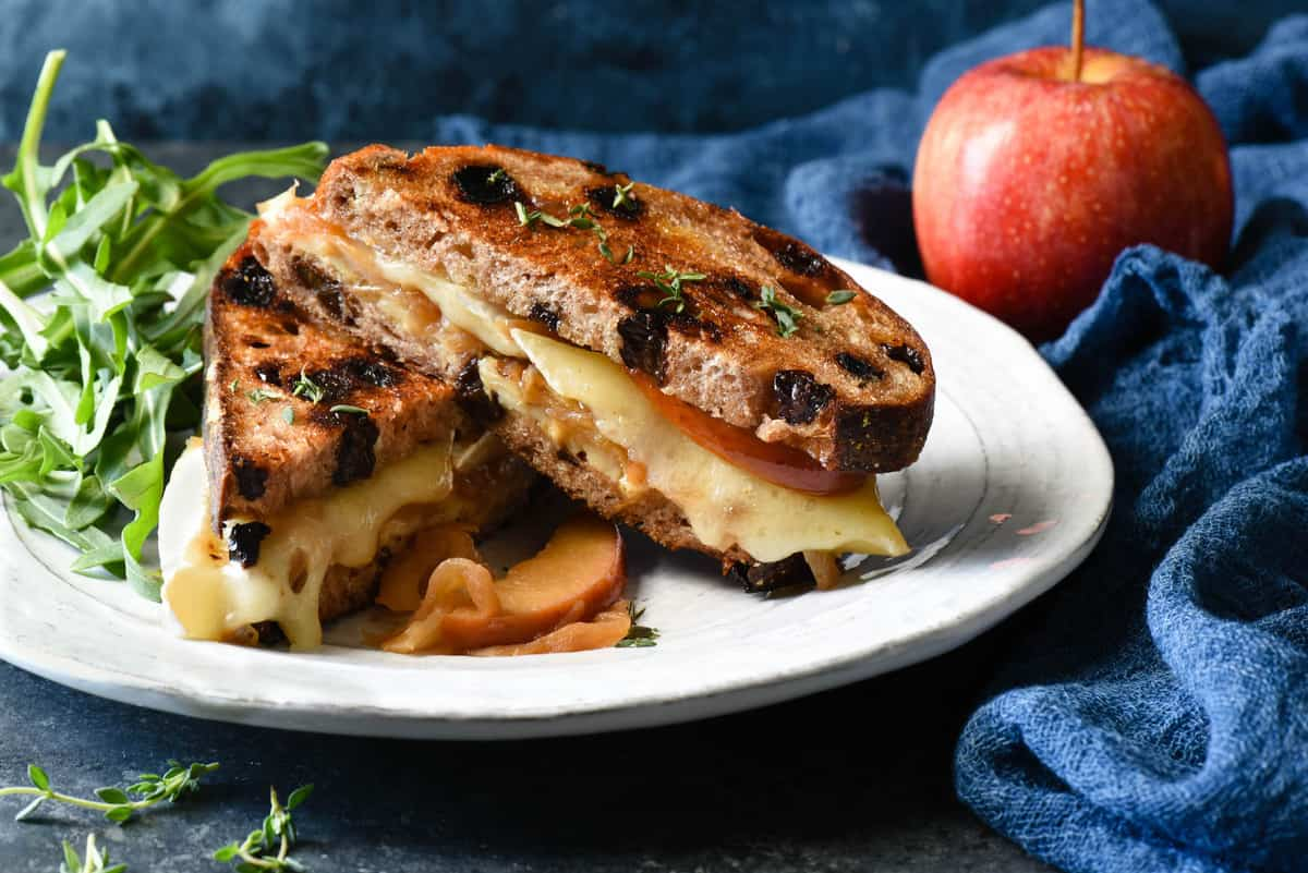 This Apple Grilled Cheese is an irresistible combination of sautéed apples, sweet caramelized onions, brie and white cheddar cheeses, Dijon mustard and walnuts. It's the best toasted sandwich you've ever made at home! | foxeslovelemons.com