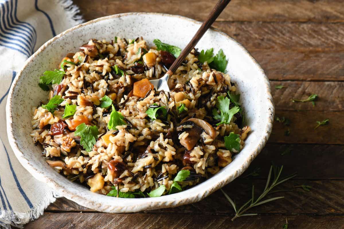 Bring a delicious but unexpected side dish to your table by making thisThanksgiving Rice Pilaf with Cranberries & Pears. This brown rice and wild rice pilaf is packed with fruit, nuts and herbs for the perfect balance of savory and sweet. | foxeslovelemons.com