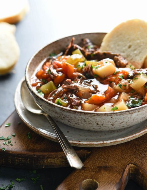 This Slow Cooker Vegetable Beef Soup is a simple, comforting and delicious Midwestern classic. A hearty meat and potatoes dinner in a bowl, this soup simmers to perfection while you're at work! | foxeslovelemons.com