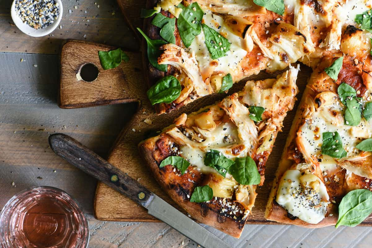 If you're making homemade pizza in the summer, you HAVE to try it on the grill! This Grilled Chicken Pizza with Mozzarella & Roasted Garlic recipe provides step-by-step instructions that will teach you how to grill pizza like a pro. | foxeslovelemons.com