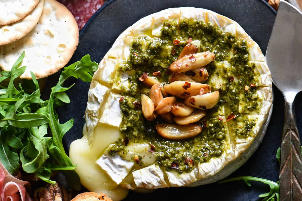 Everybody loves melted cheese, and this Savory Baked Brie takes it to the next level. Baked brie is topped with basil pesto and roasted garlic. | foxeslovelemons.com