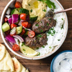 Bowl with kafta, hummus, yogurt sauce and a chopped vegetable salad on a wooden background.