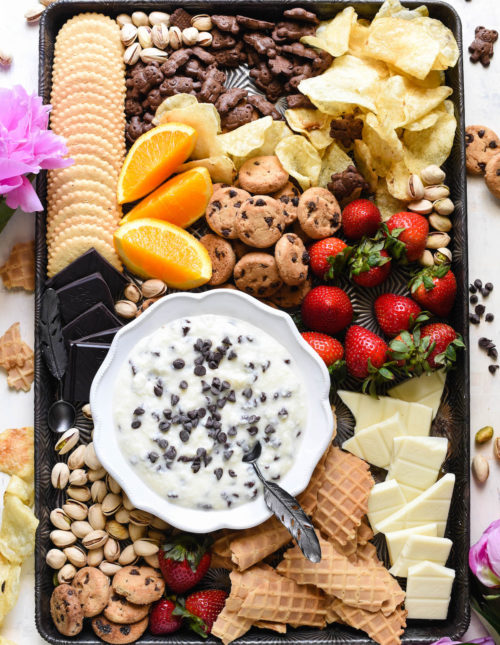 Overhead shot of large pan with bowl of dessert dip and cookies, fruit, nuts and potato chips for dipping.