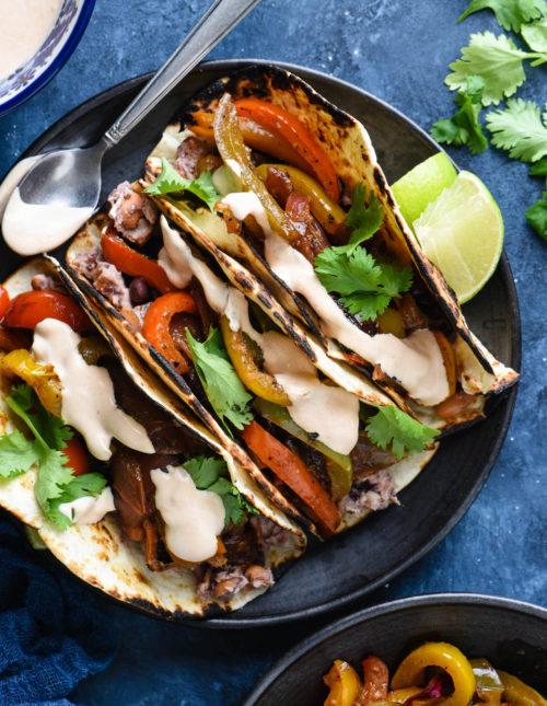 Overhead photo of three vegetarian fajitas on black plate with lime wedges.