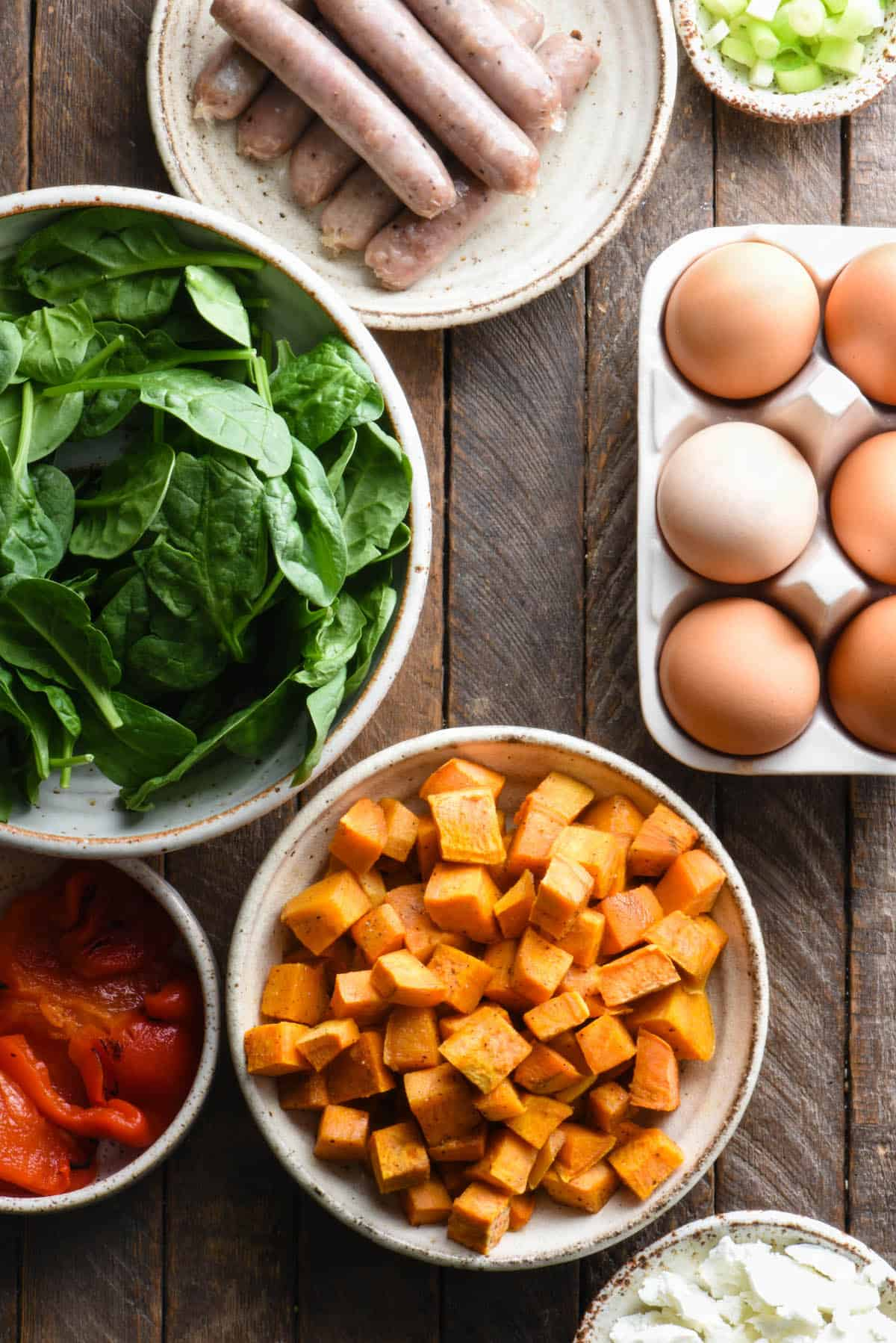 Prepped ingredients for sweet potato and egg casserole, including sausage links, green onions, baby spinach, roasted sweet potatoes and brown eggs.