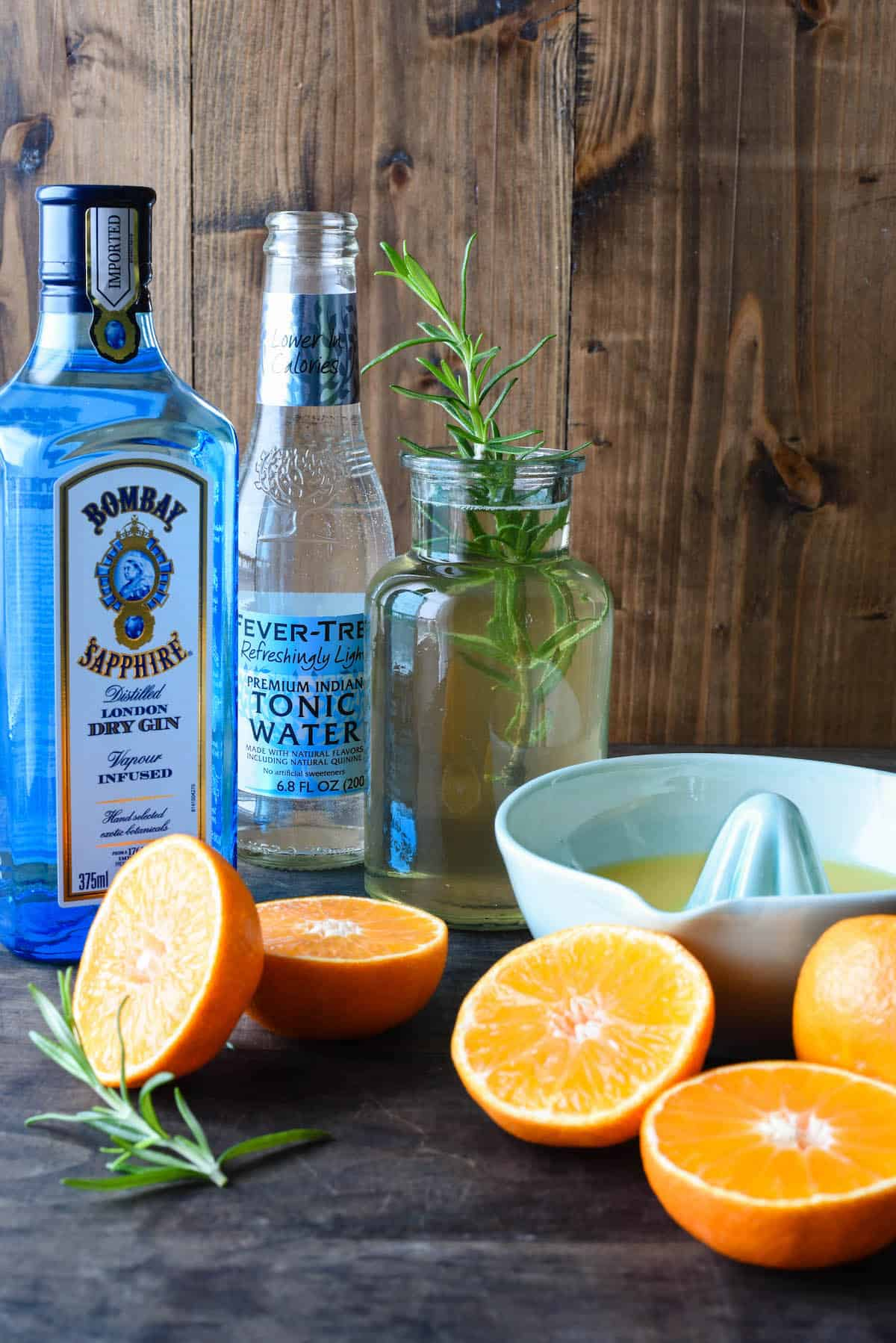 Gin and tonic water bottles, small bottle of rosemary simple syrup, ceramic juicer and cut oranges against wooden backdrop.