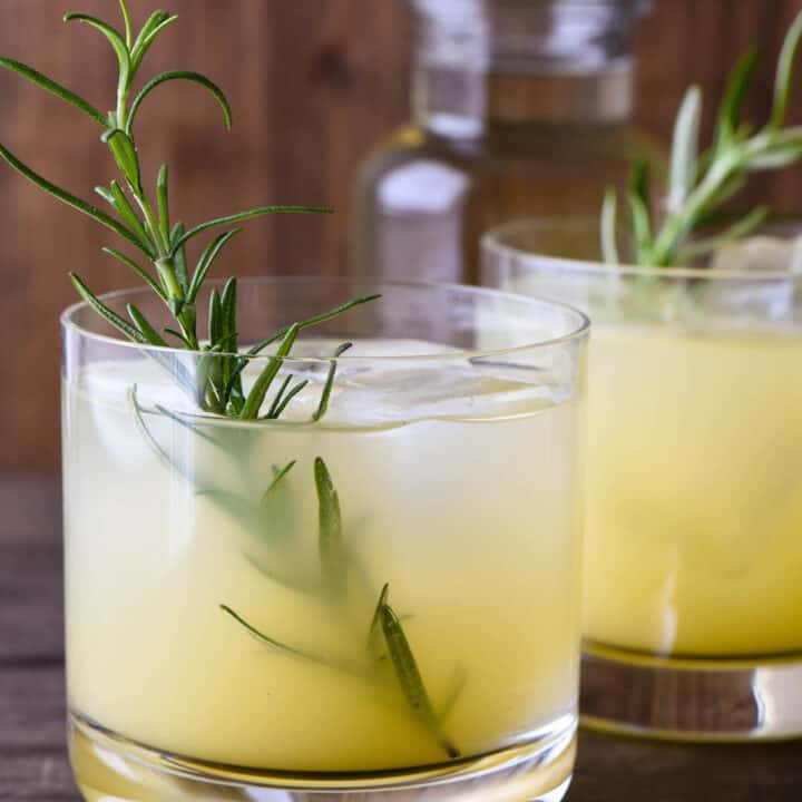 Orange hued cocktail in small glass with a rosemary sprig garnish.
