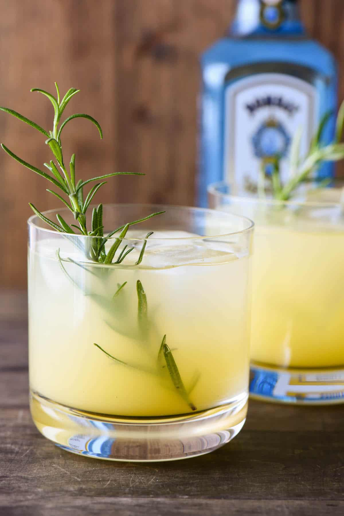 Orange hued rosemary gin cocktail with rosemary sprig garnish, and blue gin bottle in background.