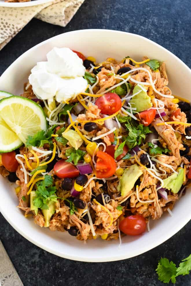 Closeup photo of crock pot burrito bowl mixture topped with cheese shreds, sour cream and lime wedges.
