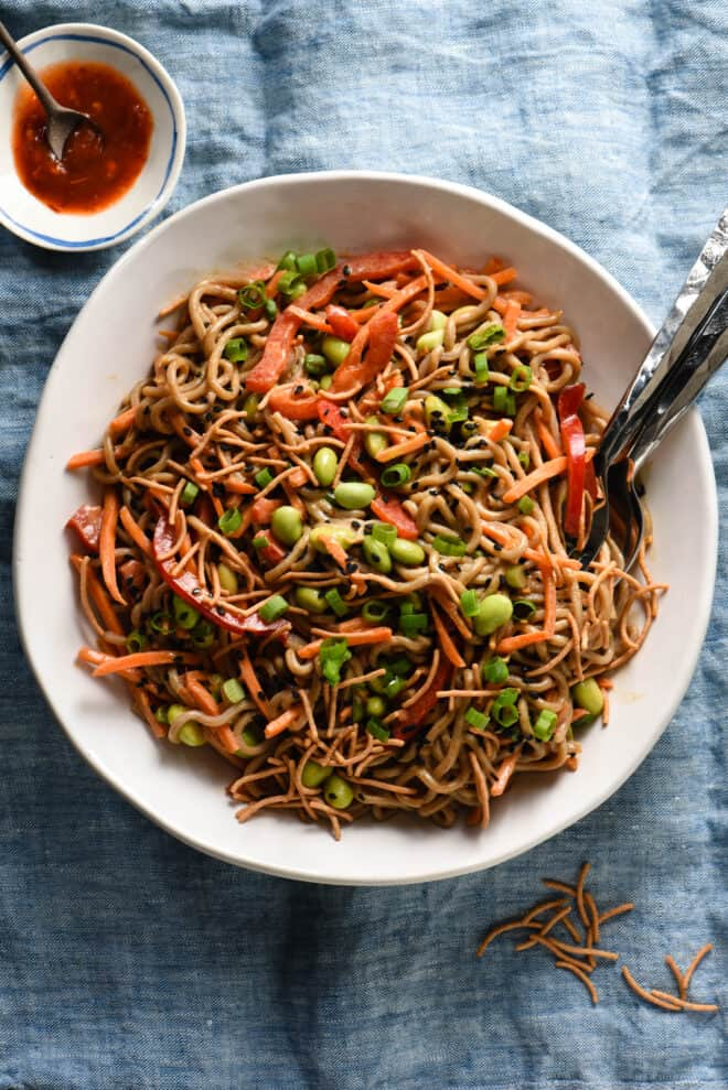Large white bowl of soba noodles tossed with vegetables, crunchy rice noodles and peanut dressing.