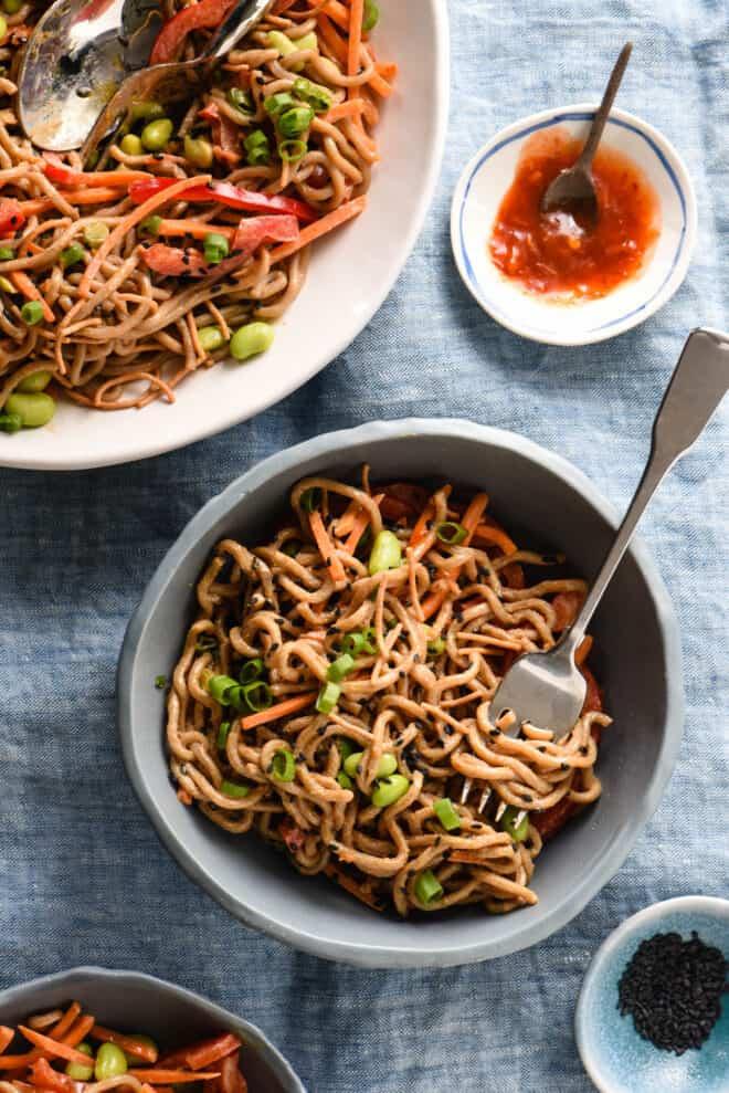 Slate blue bowl filled with Asian noodle salad, alongside larger serving bowl and small bowls of hot sauce and black sesame seeds.