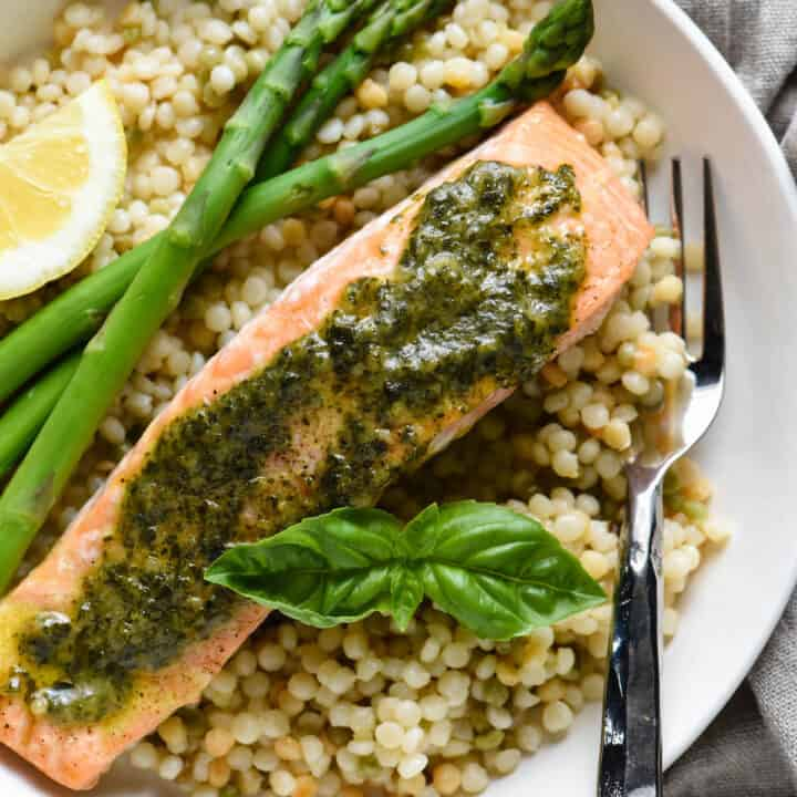Shallow white bowl filled with pearl couscous, asparagus, and salmon topped with pesto sauce.