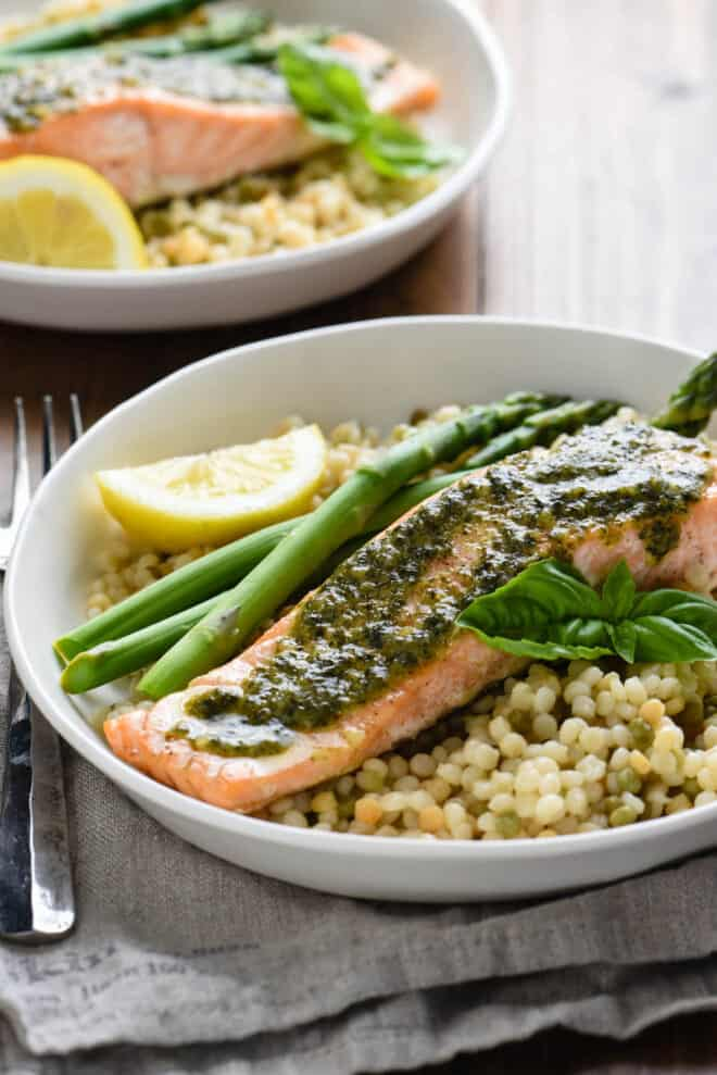 Shallow white bowl with baked fish topped with green herb sauce, tricolor couscous, asparagus, fresh basil sprig and lemon wedge.