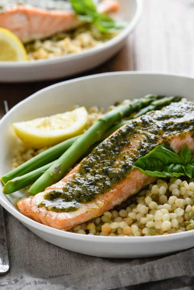 White plate filled with roasted fish with basil sauce, couscous and asparagus.