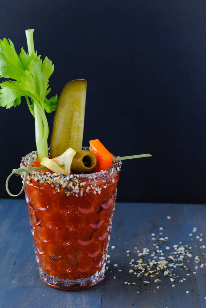 Large glass rimmed with bloody mary rim salt and filled with homemade bloody mary mix and garnishes like celery, pickles and olives.