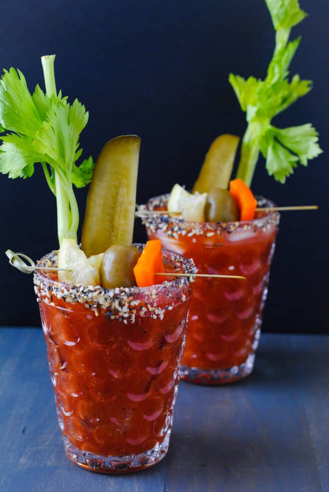 Two glasses rimmed with seeds and spices and filled with homemade bloody mix and lots of garnishes.