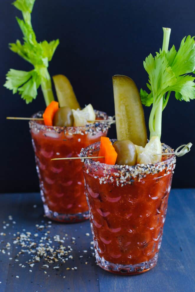 Two textured glasses crusted with bloody mary rim salt and filled with bloody mary mix, pickles, olives and celery.